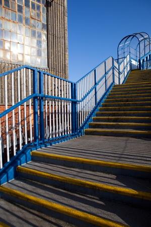 flyover: Trap-en pakhuis. voetgangers viaduct stappen met leuningen naast de oude industriële architectuur Stockfoto