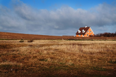 Farm house in Denmark. Home in the countryside isolated from other buildings on agriculture land or field photo