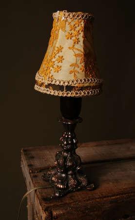 vulgar: table lamp or vintage light. vulgar retro light and shade on wood background  Stock Photo