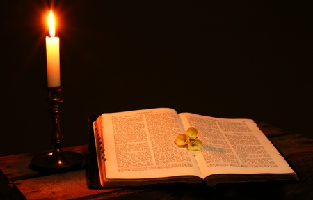 bible or spiritual  book and candle, religious scripture lit by flame  photo