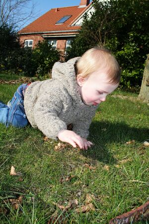 Child in garden crawling on lawn. toddler exploring nature in spring Stock Photo - 13127467