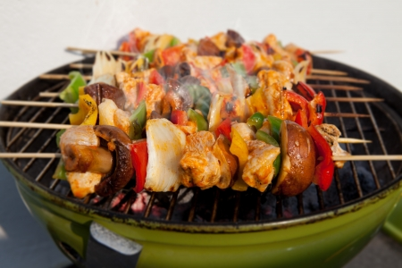 barbecuing: Bar-B-Q or BBQ with kebab cooking. coal grill of chicken meat skewers with mushroom and peppers. barbecuing dinner Stock Photo