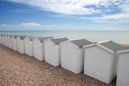 shore line: beach huts in seaside town bexhill on sea, east sussex England. small wood chalets on the coast