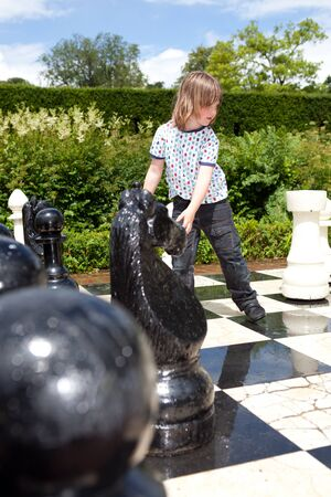 black giant: Chess game with giant chess piece. child playing strategic outdoor game on black and white board