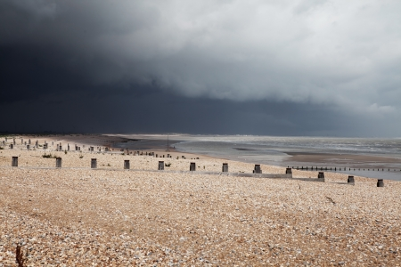 Beach in bad weather, coast with dark storm clouds. Winchelsea in england sussex with view of groyne wood pillars Stock Photo - 16240596