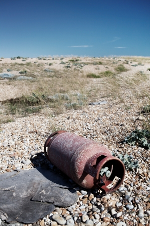 gas cylinder: metal scrap abandoned on the beach. discarded iron pollution and enviromental hazard