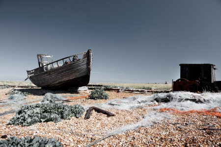 fishing huts: abandoned fishing trawler on beach. old ship wreck on english south coast in dungeness