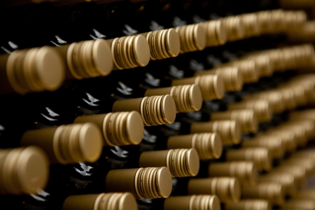 Wine bottles in a row. tops of alcohol in winery or cellar photo