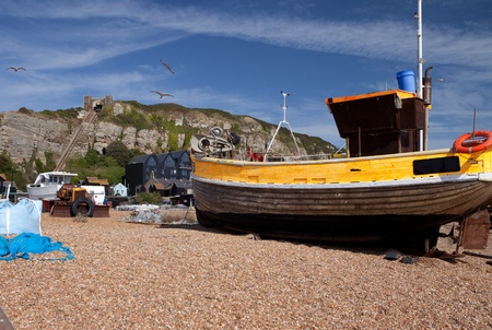 fishing cabin: Fishing trawler or boat on beach in hastings with hill in background. yellow wooden ship and fishing industry