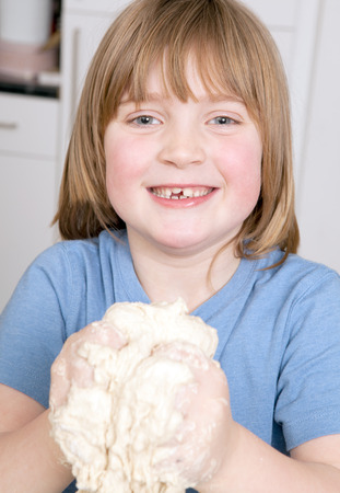 bread making with child kneading dough. cooking pastry product at home photo