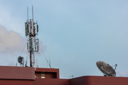Electronic communications and cell phone tower under partially cloudy sky photo