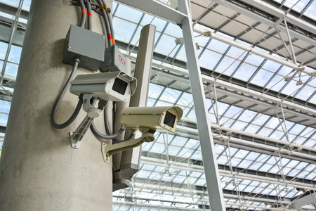 ownership and control: CCTV camera or surveillance operating with electric door in back Stock Photo