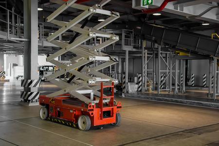 distribution warehouse hall with hydraulic scissors lift platform Foto de archivo