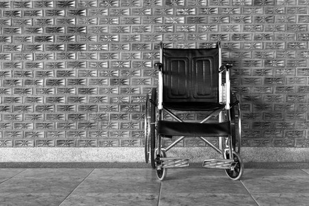 Black and white wheelchair rolls on the sidewalk. Imagens