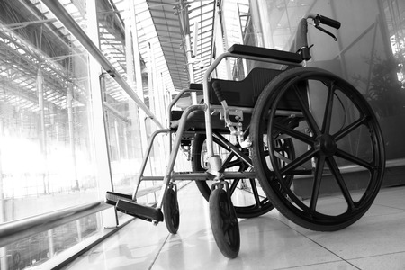 invalidity: Black and white Wheelchair service in airport terminal