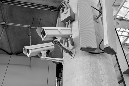 ownership and control: black and white CCTV camera or surveillance operating with electric door in back Stock Photo