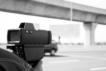 cars on the road: black and white catch speeding drivers with a radar gun