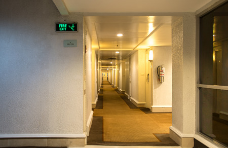 Emergency fire exit sign and corridor in the hotel