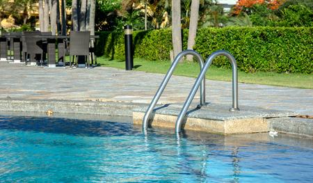 pool bars: Grab bars ladder in the blue swimming pool Editorial