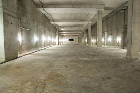 cemento: Interior vacío sala de garaje industrial con piso de concreto y la pared de fondo Editorial
