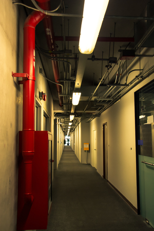 Long corridor interior and fire extinguish equipment, vintage color style Editorial