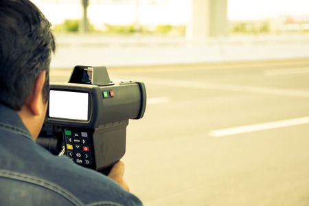 catch speeding drivers with a radar gun, vintage color style 写真素材