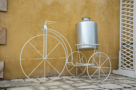 wall decor: white decor bicycle on the rock wall background., vintage color style Stock Photo