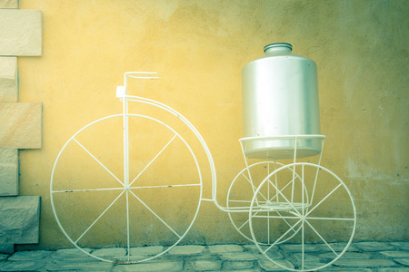 light on white decor bicycle on the rock wall background., vintage color style Stock Photo