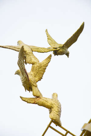 set free: gold Sculpture of a Dove Being Set Free Stock Photo