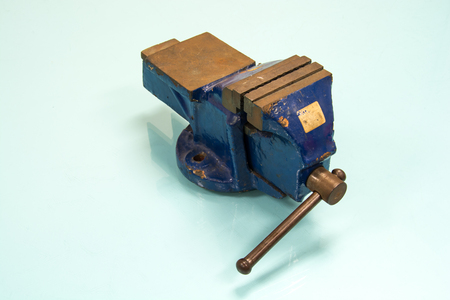 Blue steel vise on table background