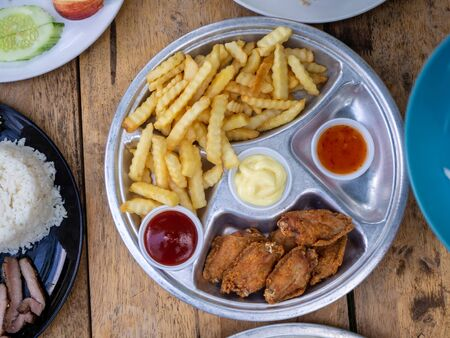 The fried chicken drumstick and french fries on wooden background. Imagens