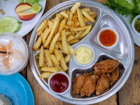 The fried chicken drumstick and french fries on wooden background.