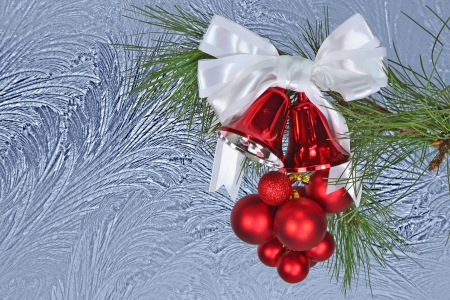 Red Christmas bells and Christmas balls with white bow against a  window frost background  Stock Photo - 16296808