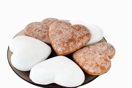 Heart-shaped  ginderbread cookies with sugar icing on a plate, isolated on white background. photo