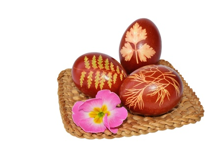 Three Easter eggs dyed with onion skin on a small straw mat Stock Photo - 17992043