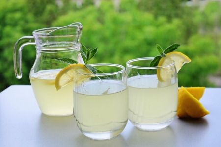Citrus lemonade in pitcher and two glasses of refreshing  lemonade on the table