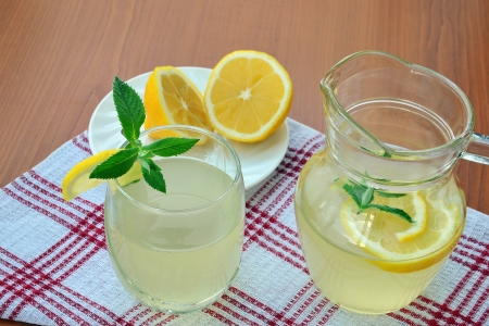 Refreshing summer lemonade with lemon in glass and pitcher  photo