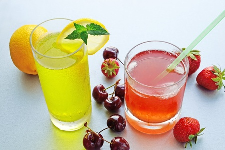 Two glasses of ice-cold fruit lemonade and fresh fruits  photo