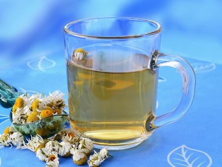 El t� de manzanilla en la taza de cristal con flores secas de manzanilla photo