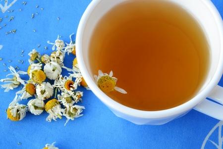 El t� de manzanilla en la taza blanca y flores de manzanilla secas photo