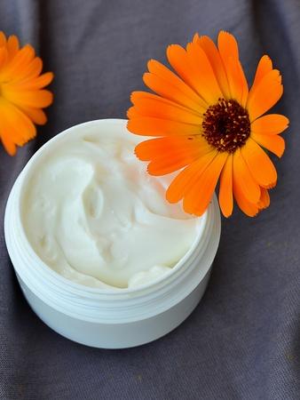 cremas faciales: Tarro de crema facial hidratante y fresca flor de caléndula Calendula crema cosmética