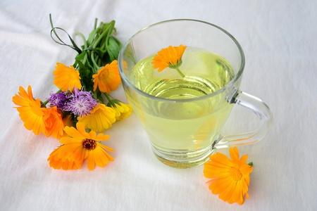 botanical remedy: Marigold - Calendula tea and a small bouquet of marigold  flowers