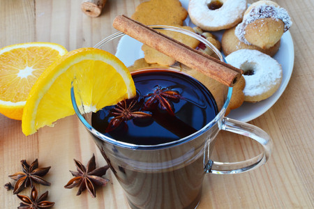 Mulled wine with spices, cookies and orange on wooden table. Shallow DOF. photo