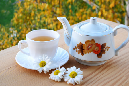 Cup of herbal tea and teapot on a wooden table.