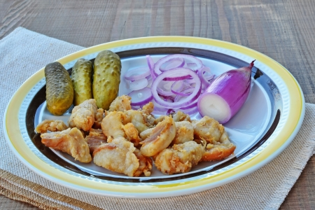 greaves: Plate of fried pieces of pork greaves with red torpedo onions and pickles on wooden table.