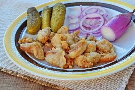 chicharrones: Frito trozos de chicharrones de cerdo con cebollas rojas de torpedos y encurtidos.