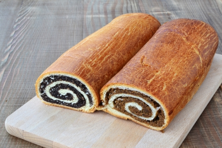 Poppy seed and walnut rolls on chopping board and wooden table  Фото со стока