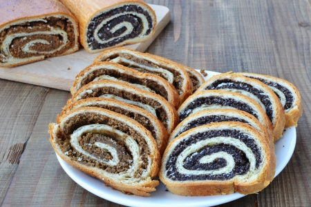 Sliced poppy seed and walnut rolls on wooden table