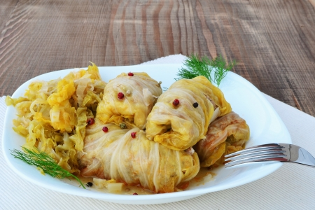 Cabbage rolls filled with minced meat and rice on plate, over wooden table. Фото со стока