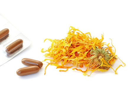 botanical remedy: Dried calendula flowers and pills isolated on white background  Stock Photo